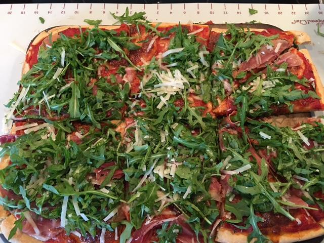 Pizza mit Rucola, Parmesan und Parmaschinken