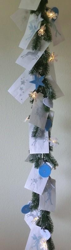 Tannengirlande mit handbemalten Papiertüten und Lichterkette geschmückt