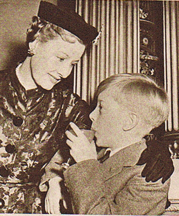 "Irene Dunne distracts young Andrew (""The Mudlark"") Ray from a tomato juice during the Friday Press reception and get-together at Londonderry House"
