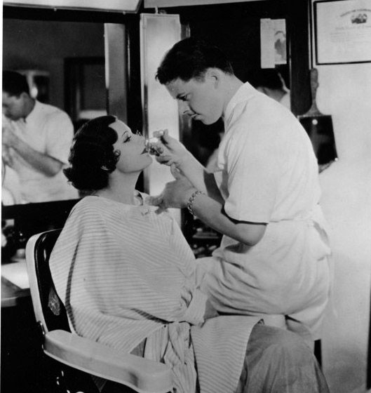 ca.1930 - with makeup artist Mel Berns. Irene gets an eyelash curl.