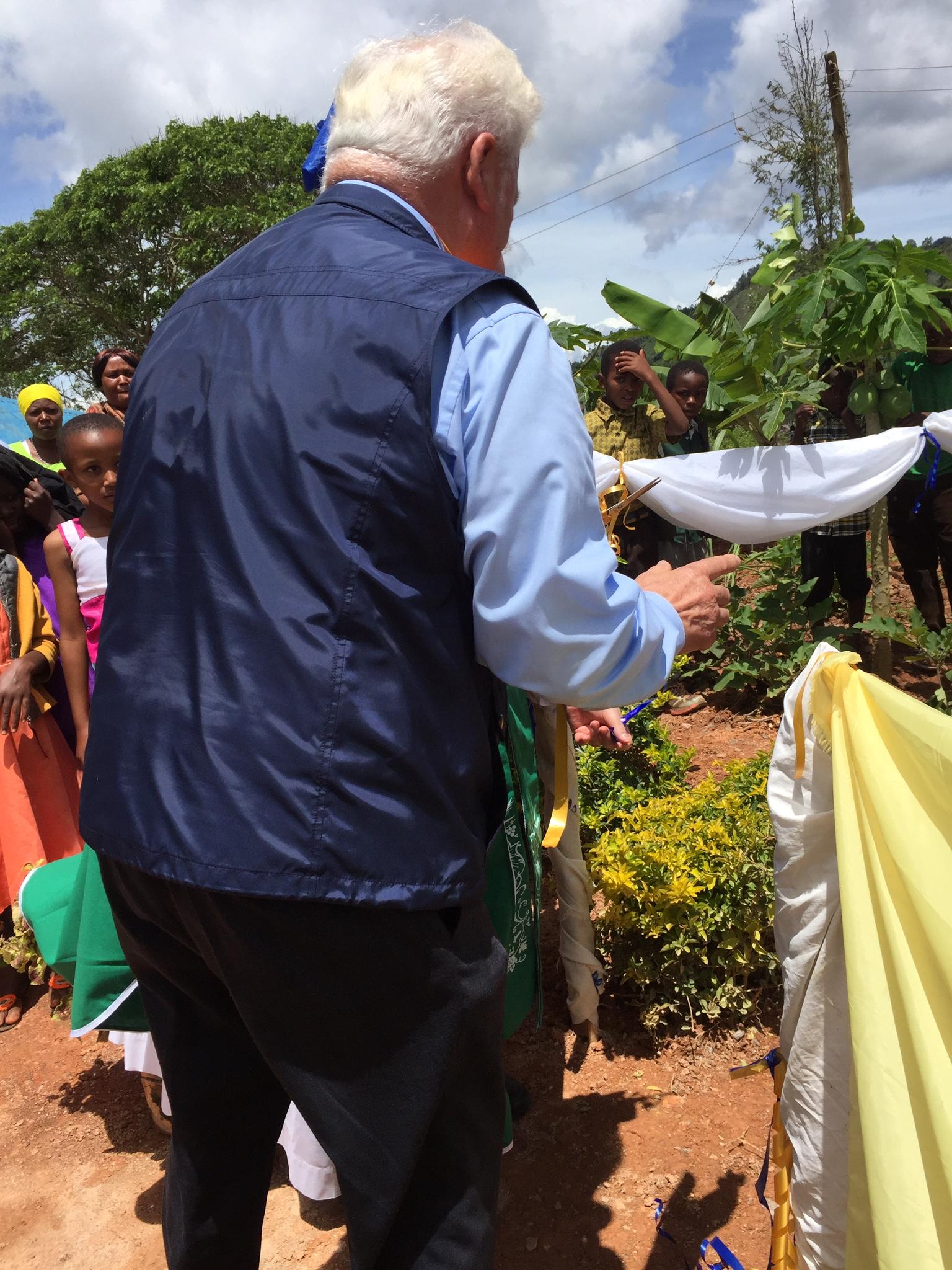 Johannes Besche schneidet das Band zur Eröffnung durch und übergibt den Bewohnern des Dorfes das Wasserprojekt