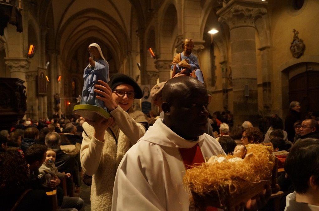 P. Yves Tano va installer l'enfant Jésus à la crèche