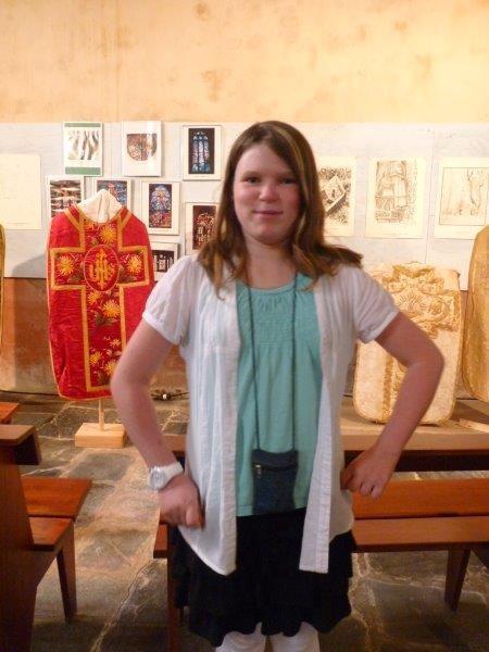 Magdaléna, tout sourire, pend la pose devant l'exposition des vêtements liturgiques