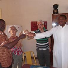 Partage de l'eau de l'étranger en 2015 à Réo (à droite, le P. Roger, en soutane blanche)