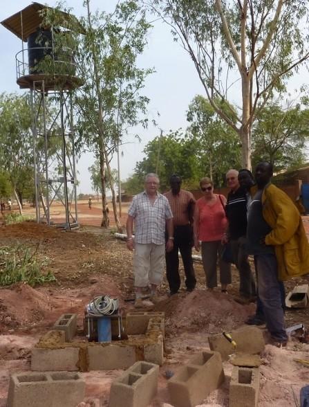 08/12/2015 - P. Michel N'Do fait découvrir le chantier à Jean-Jacques, François et Monique : ici,  la tête du puits, avec en arrière-plan, le château d'eau