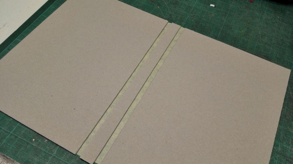 Ein Stück Graupappe wird dem Maß des Buchblocks entsprechend zugeschnitten und fixiert...
