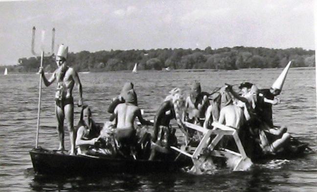 Schergen  bringen Neptun und sein Gefolge hier mit einem Tretboot über das Wasser  zum Taufplatz (Quelle:Latte)
