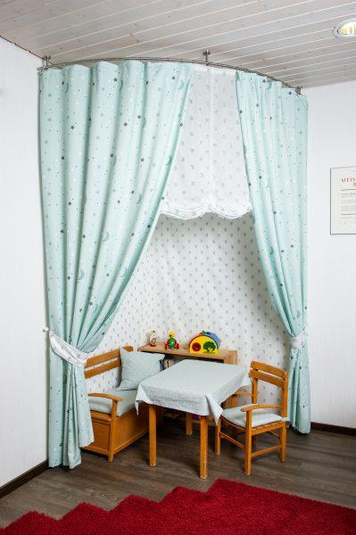 Die Spielecke mit türkisen Vorhängen und Sitzgelegenheiten