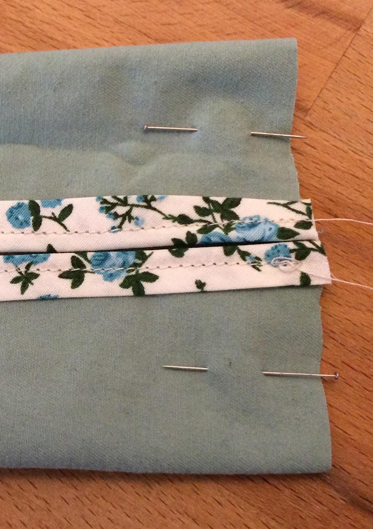 Dann faltet ihr die kurzen Seiten mit dem Schrägband zur Mitte, sodass die schöne (rechte) Stoffseite innen liegt, und...