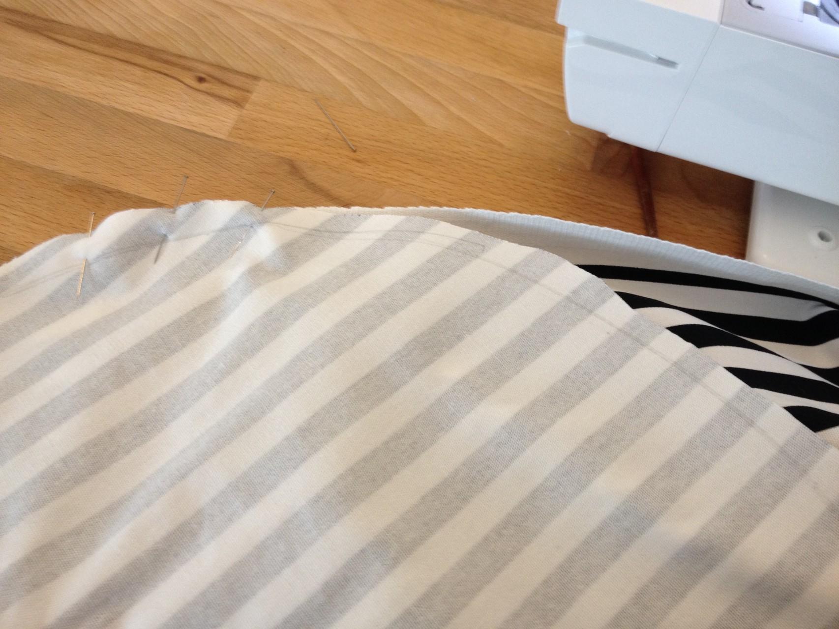 Danach die Breite eures Rechtecks rechts auf rechts an das runde Bodenteil stecken (hilfreich sind viele Nadeln in kurzen Abständen) und festnähen.