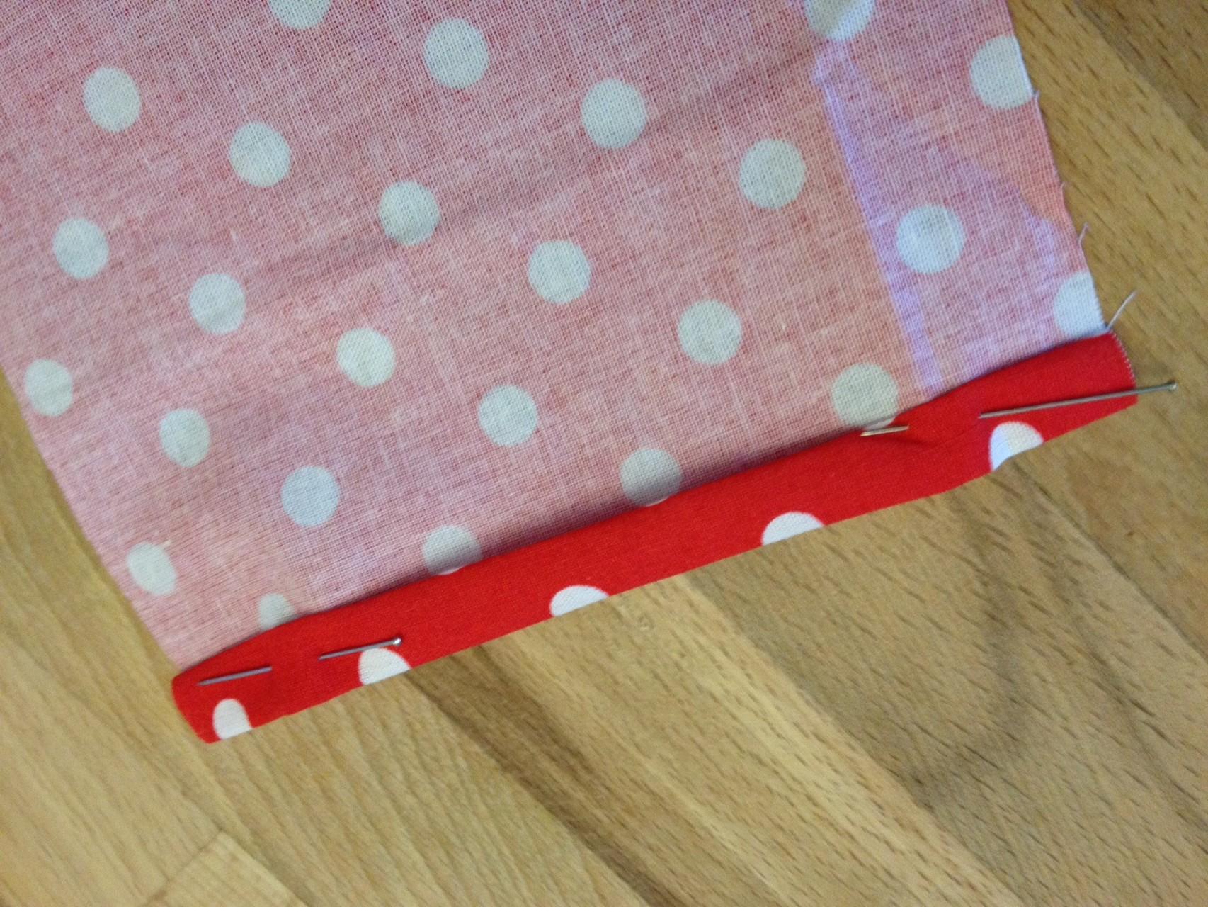 Anschließend schlagt ihr auf beiden Seiten die kurzen Kanten zweimal jeweils ca. 1cm nach innen um und steckt es fest.