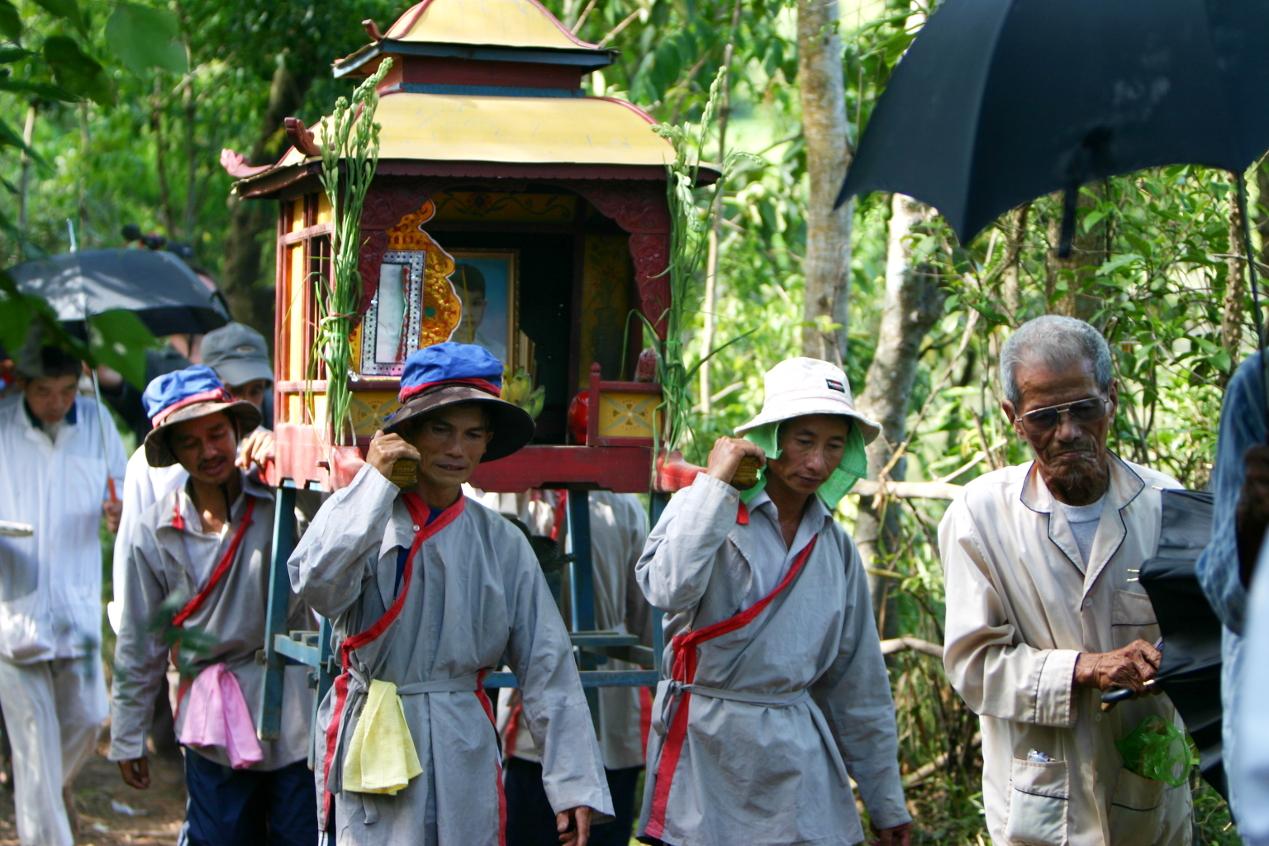 Ein Schrein mit dem Bildnes des getöteten Jungen wird durchs Dorf getragen.