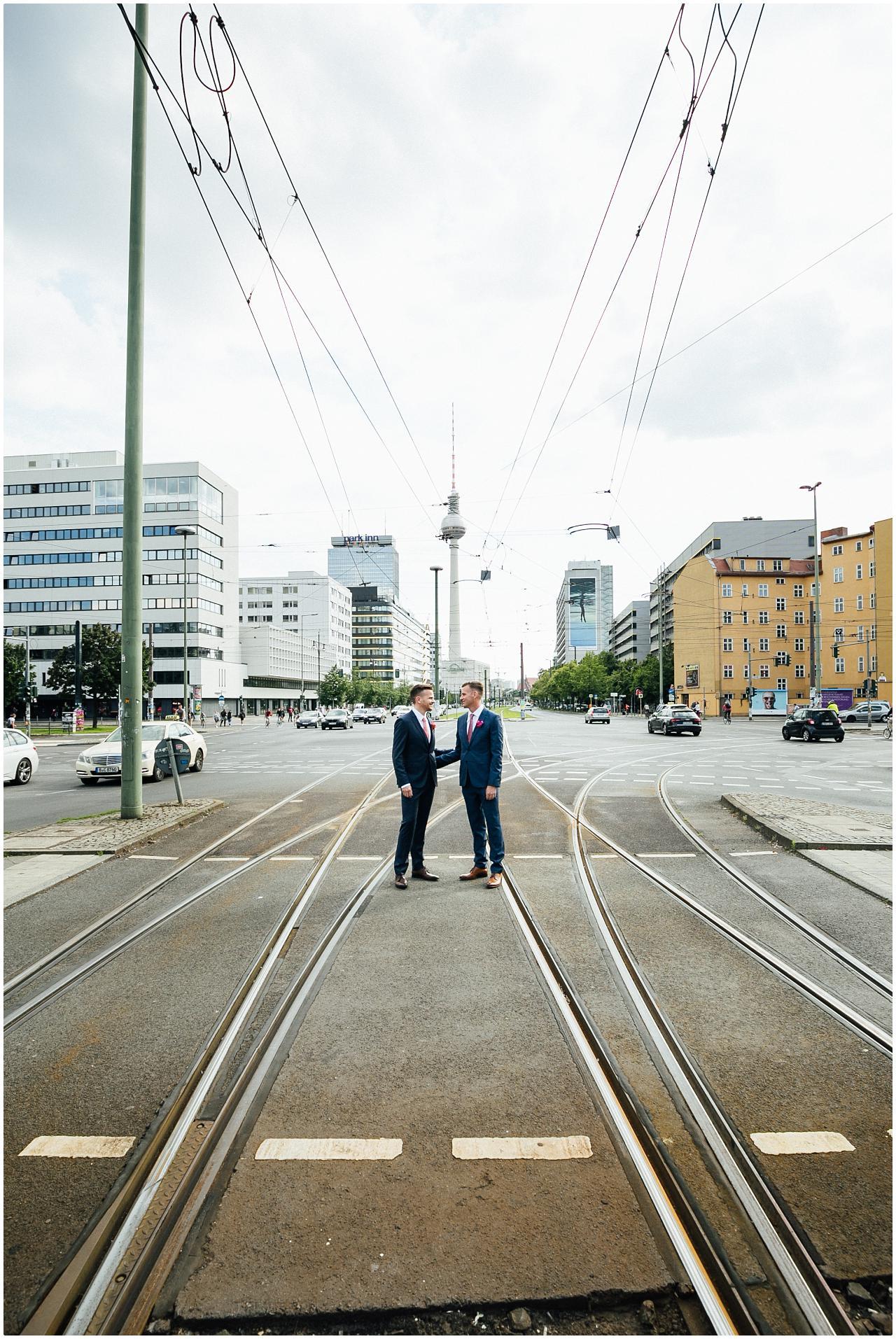 Gleichgeschlechtliches Brautpaar posiert auf den Schienen der Tram vor dem Alexanderplatz in Berlin