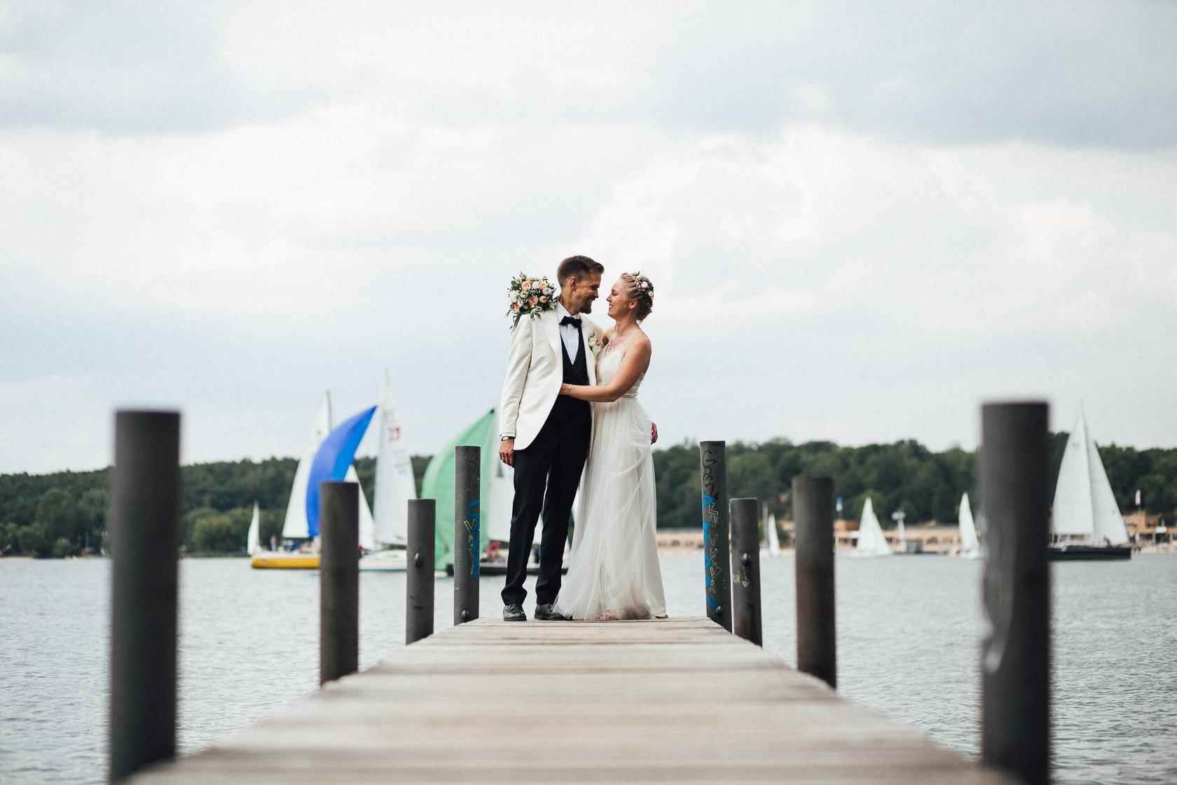 Verliebtes Brautpaar umarmt sich am Wannsee an einem Bootssteg