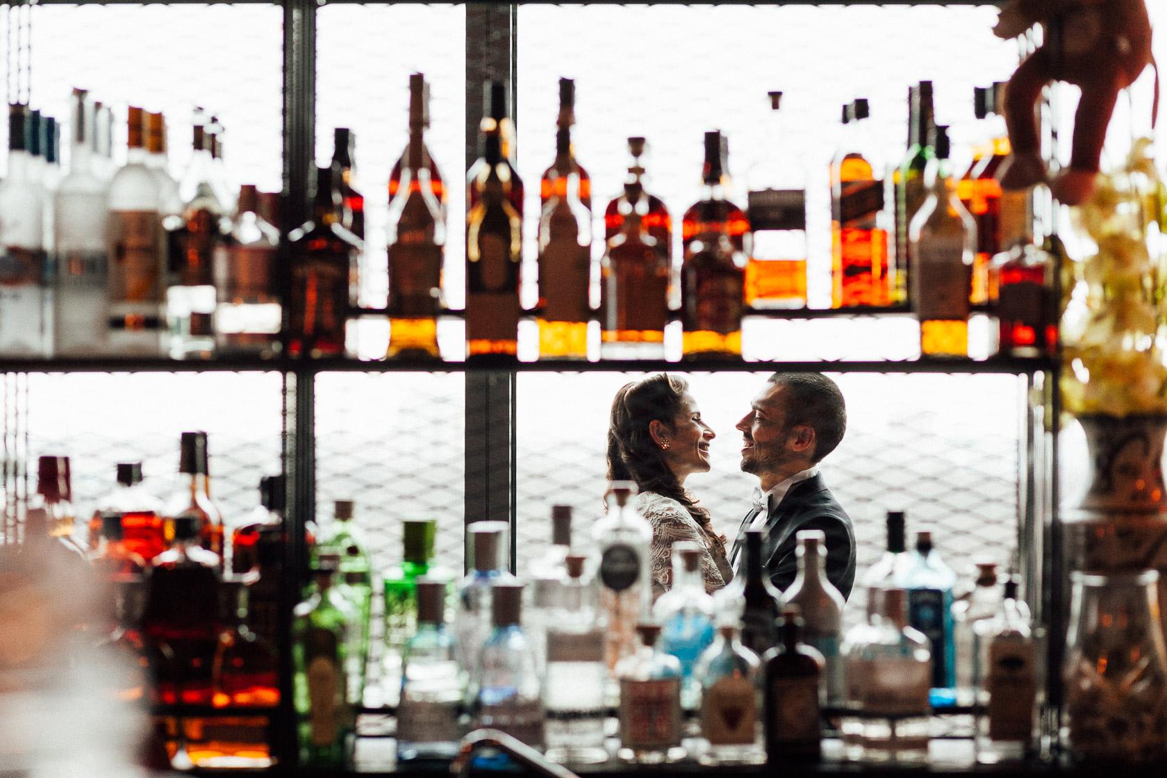 Braut und Bräutigam lachen gemeinsam hinter eine paar bunten Flaschen in der Monkey Bar in Berlin