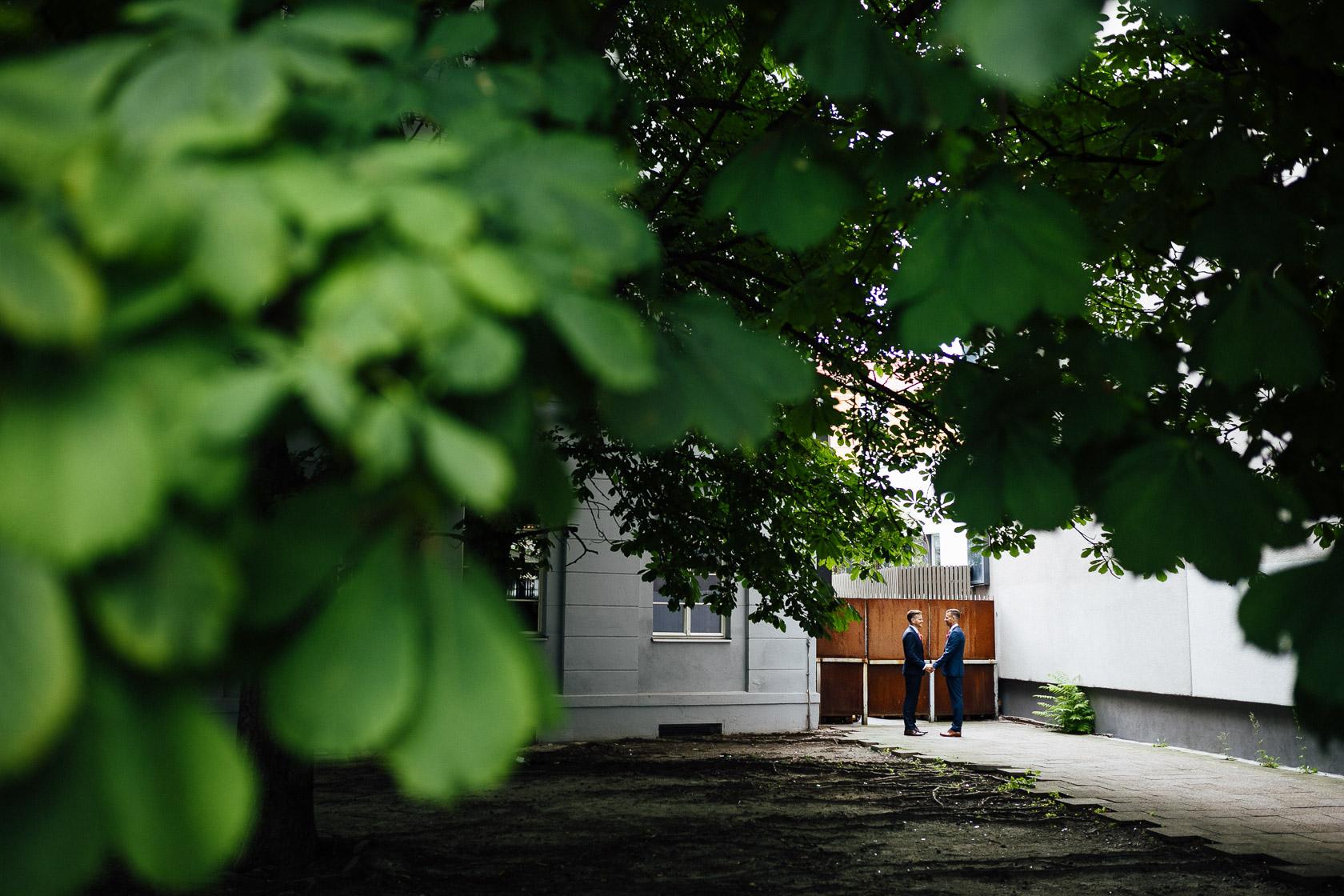 Elegant gekleidetes gleichgeschlechtliches Brautpaar vor dem Eingang zum The Grand in Berlin Mitte