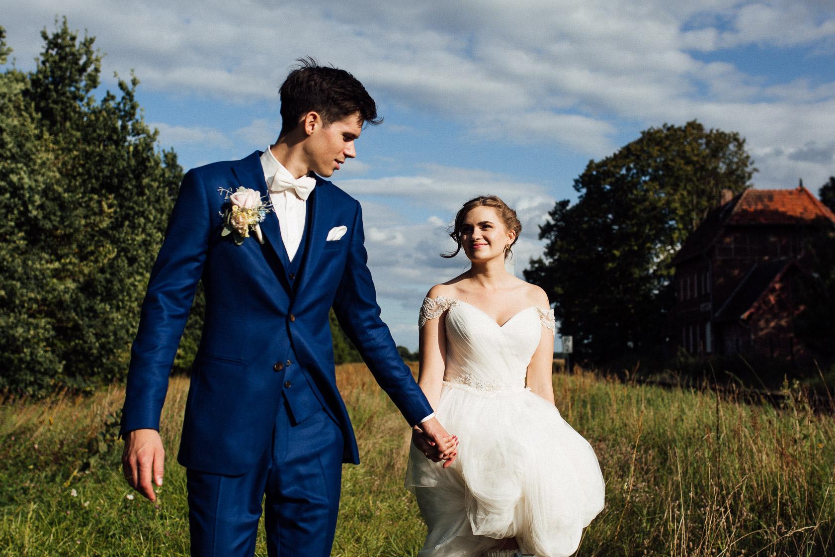 Bräutigam in blauem Anzug führt eine glückliche Braut an der Hand durch ein Weizenfeld