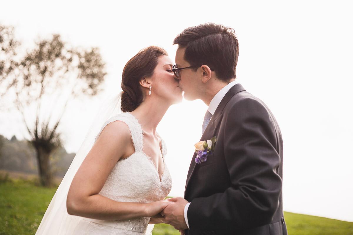 Brautpaar gibt sich im Gegenlicht einen Kuss.