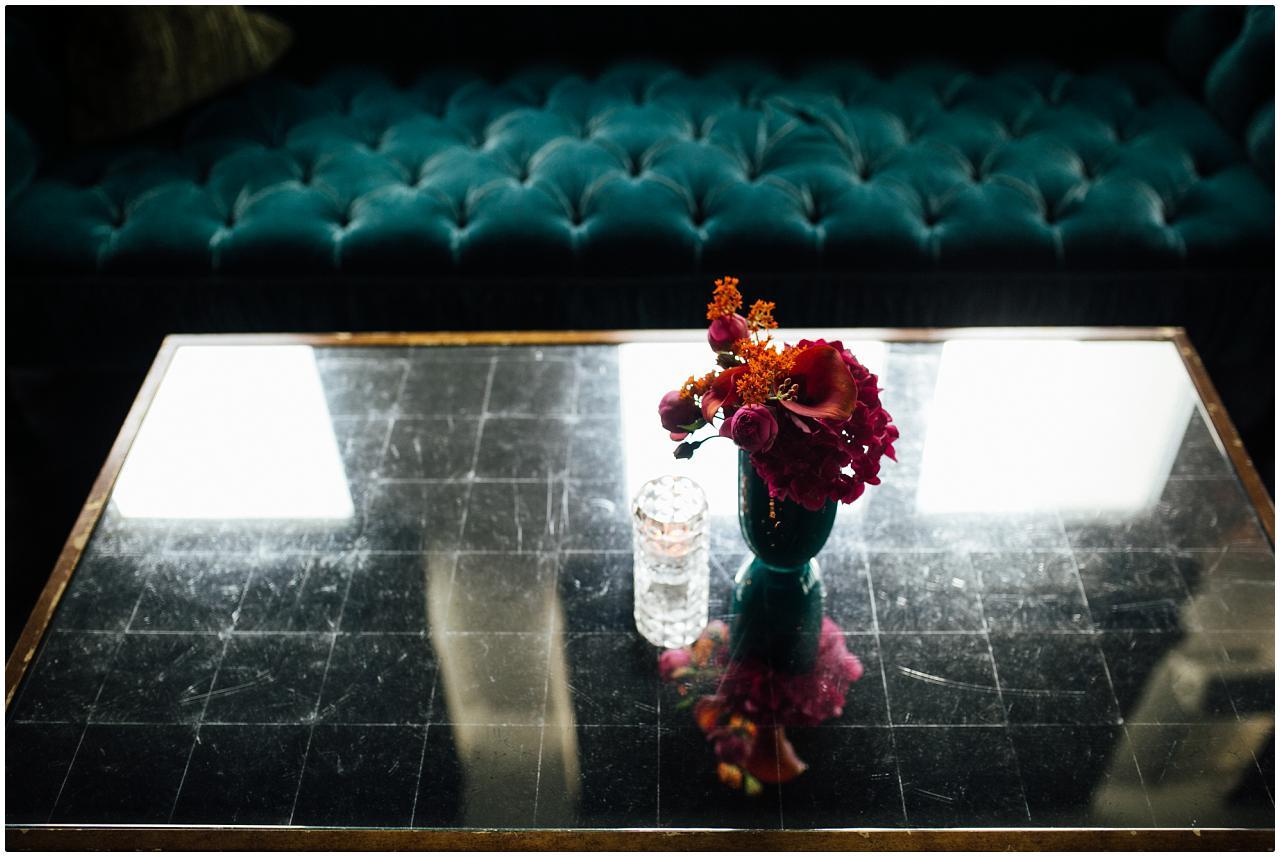 Ein wunderschönes, pinkes Blumengesteck auf einem verspiegelten Tisch vor einem grünen Sofa