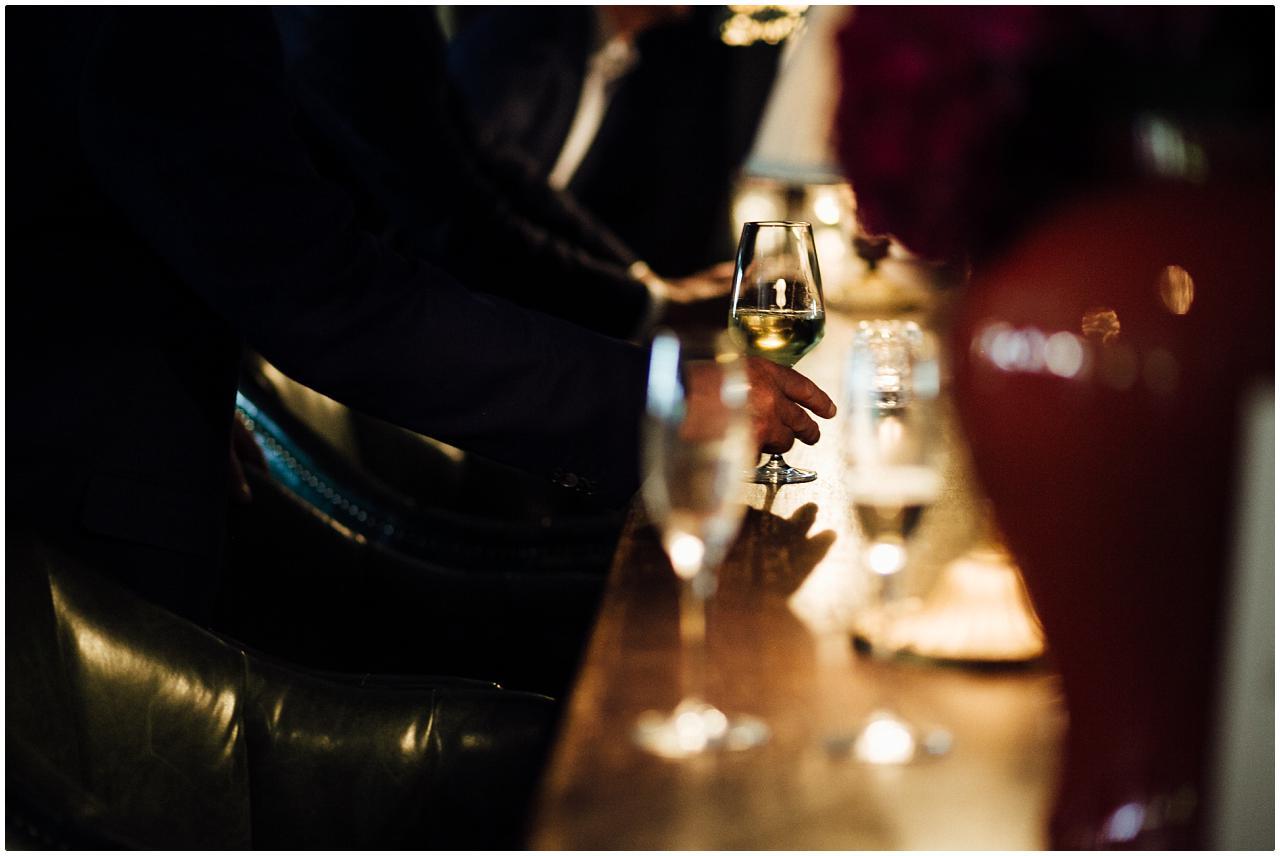 Ein Gast nimmt ein Glas Weißwein von der Theke
