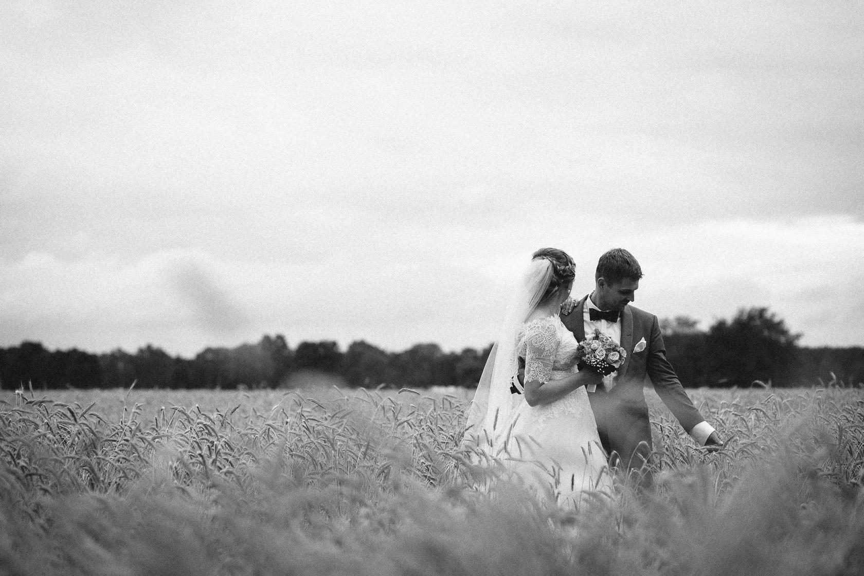 Braut und Bräutigam stehen im Roggenfeld in der Nähe von Berlin