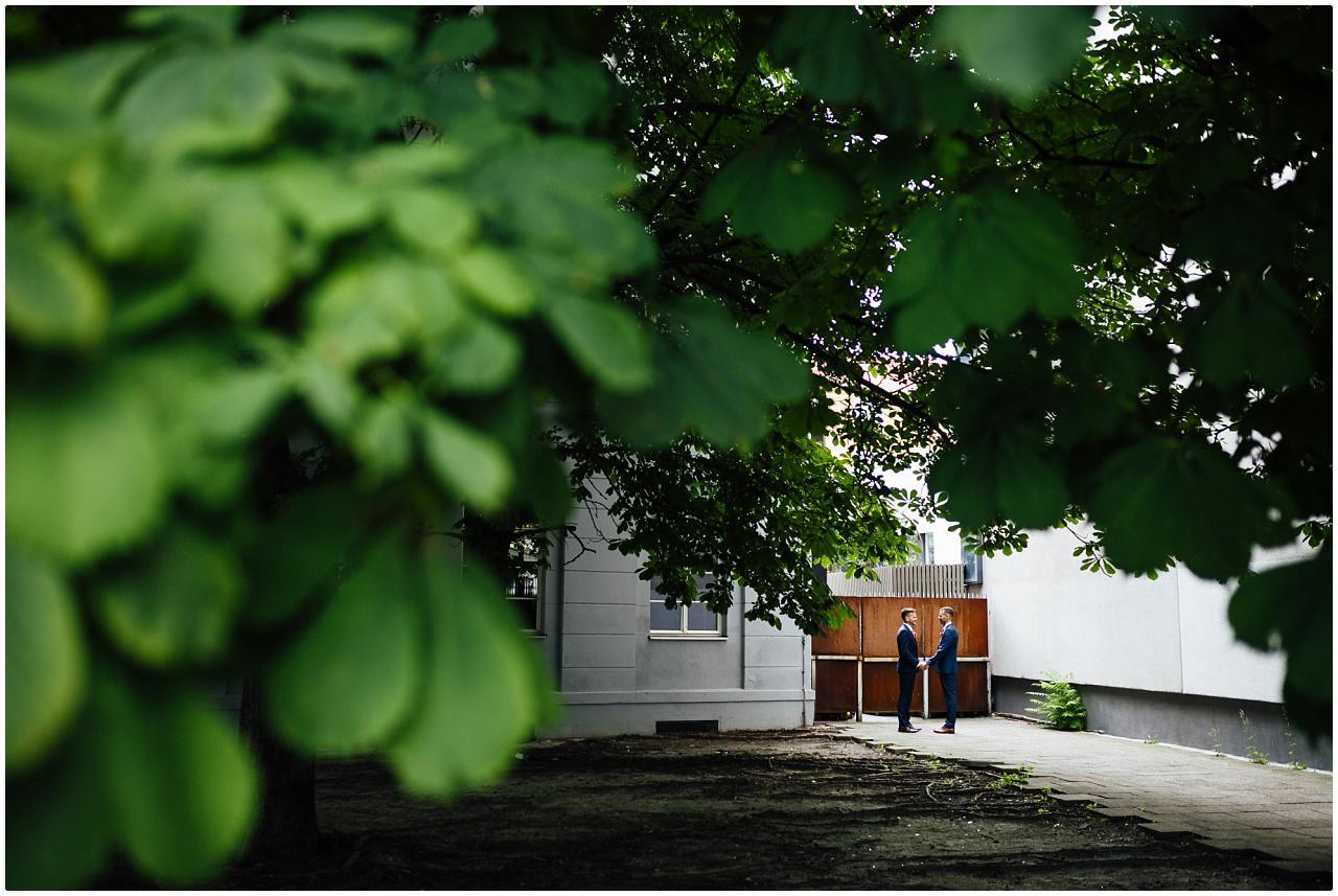Gleichgeschlechtliches Brautpaar hält sich an den Händen vor der Tür des The Grand in Berlin Mitte