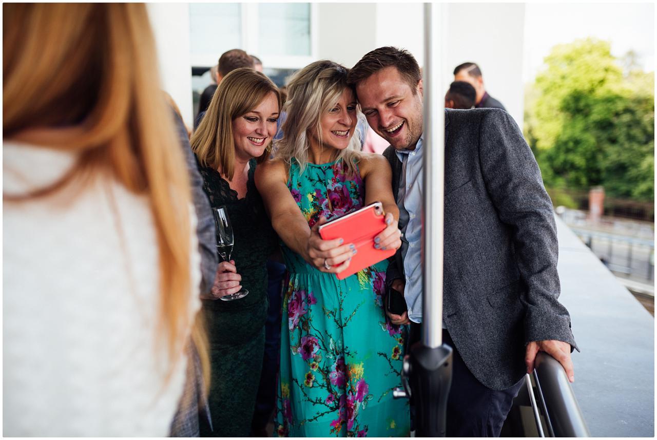 Zwei Frauen und ein Mann posieren für ein Selfie