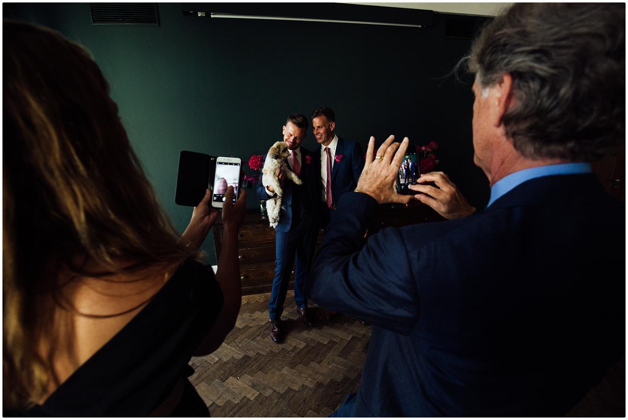 Das Brautpaar und der Familienpudel werden von Hochzeitsgästen mit Handys fotografiert