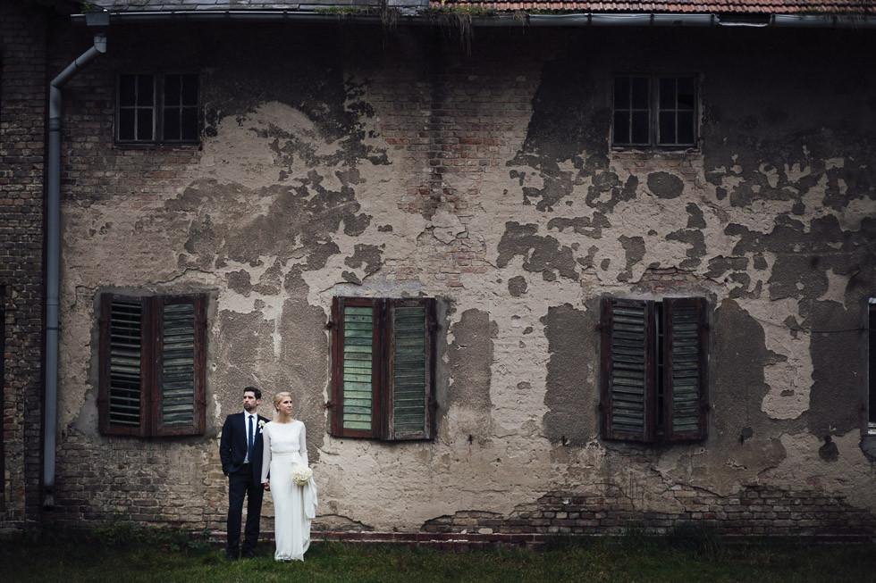 Inniges Brautpaar posiert vor abgerockter Fasade neben Schloss Kartzow