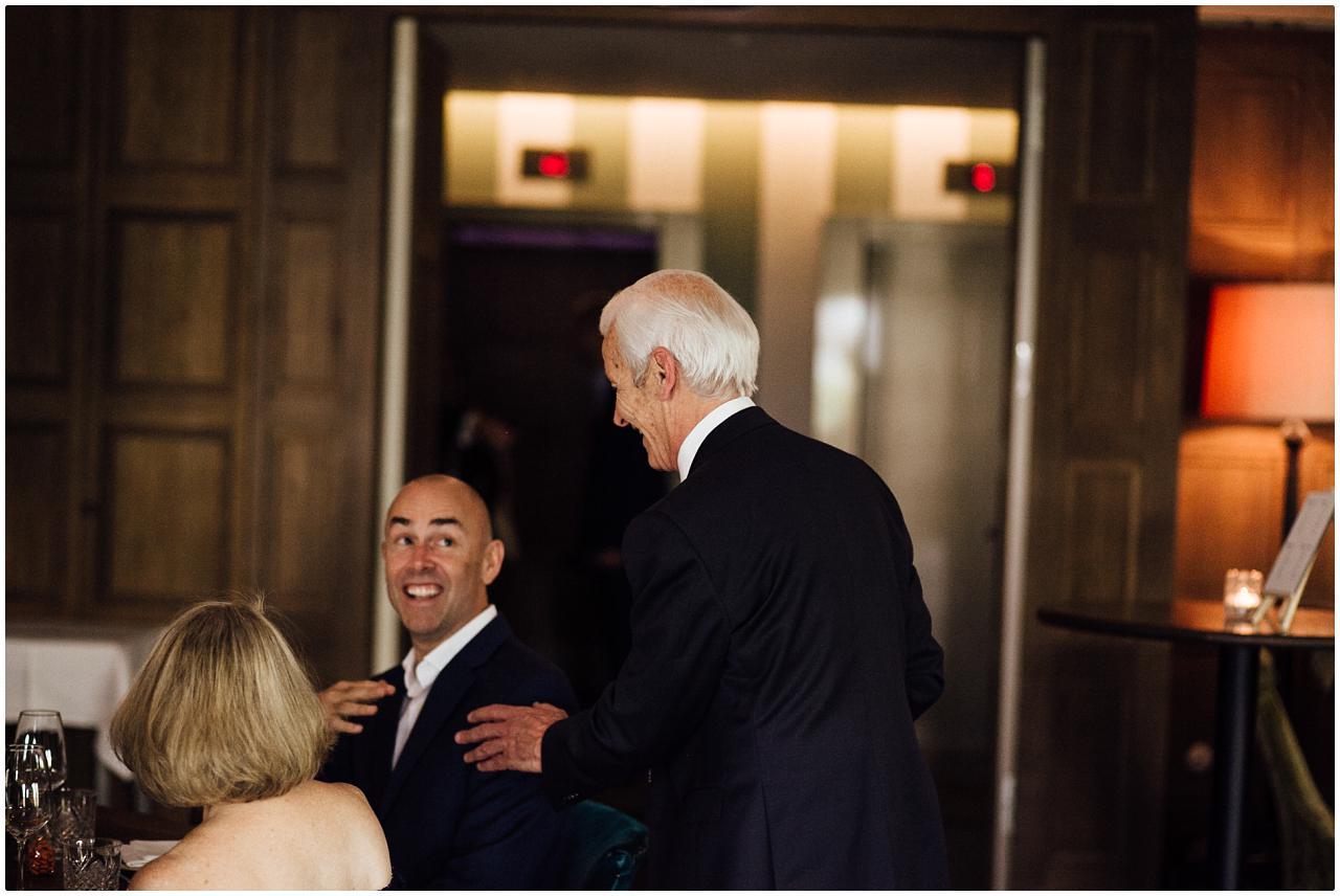 Ein Brautvater begrüßt sehr herzlich einen Gast mit Glatze