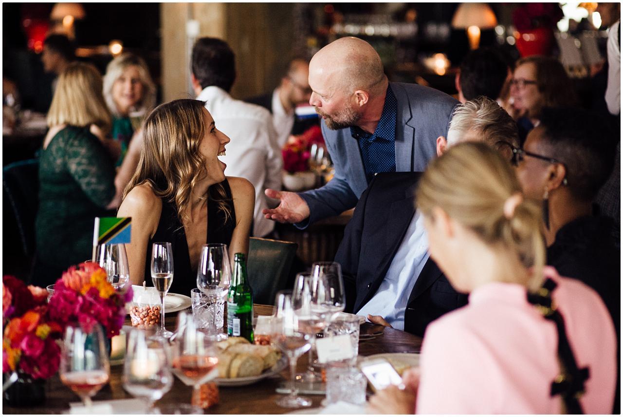 Zwei Hochzeitsgäste lachen intensiv miteinander