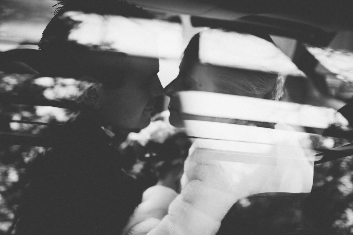 Brautpaar durch die Scheibe des Delorean beim Küssen fotografiert