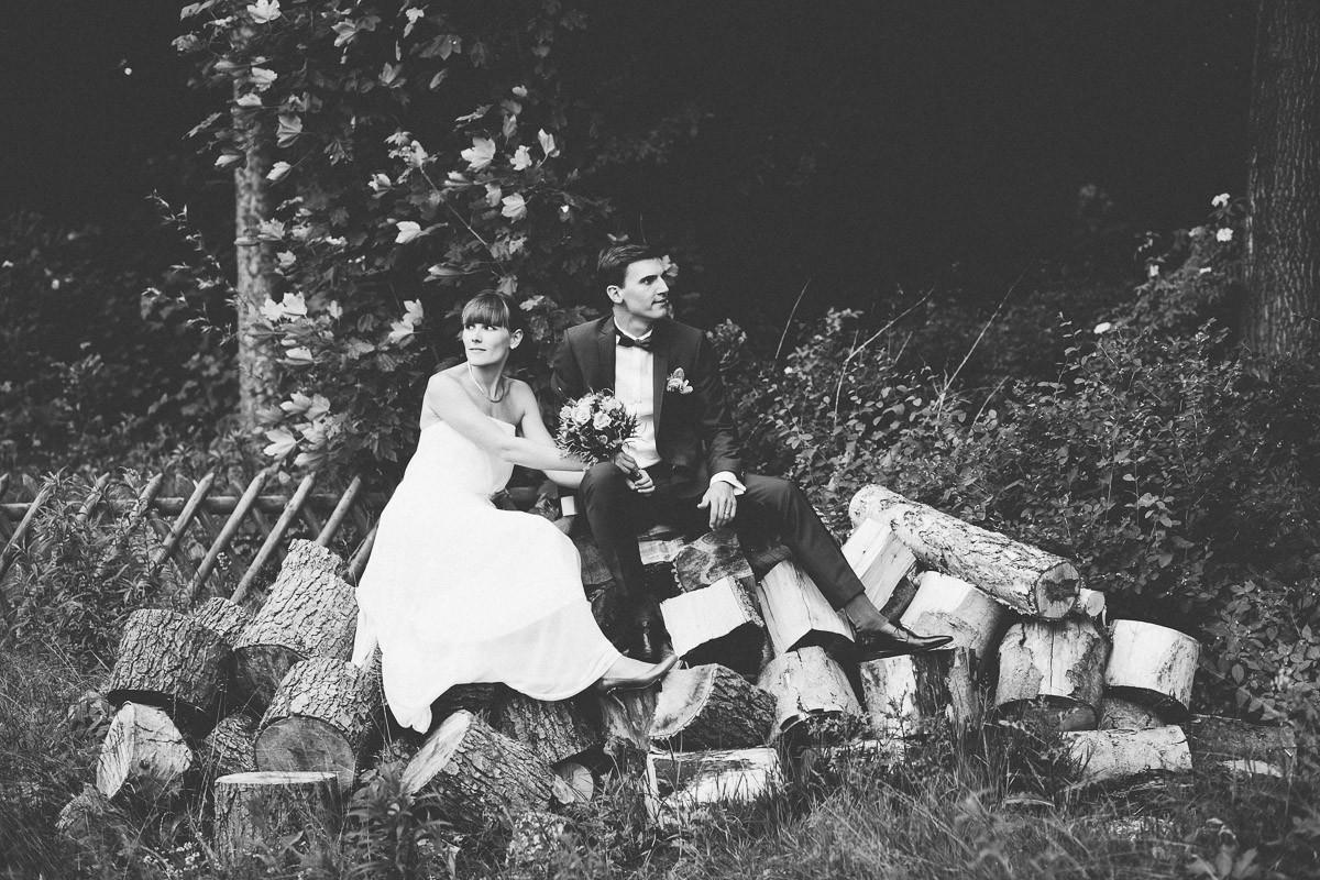 Brautpaar entspannt sich nach der Trauung im Cafe Wildau auf einem Holzstapel