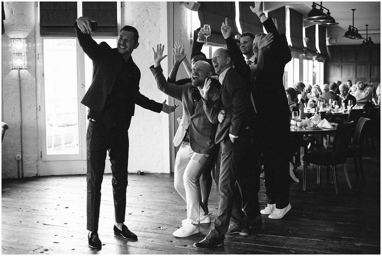 Sieben stilsicher gekleidete Hochzeitsgäste posieren für ein Foto