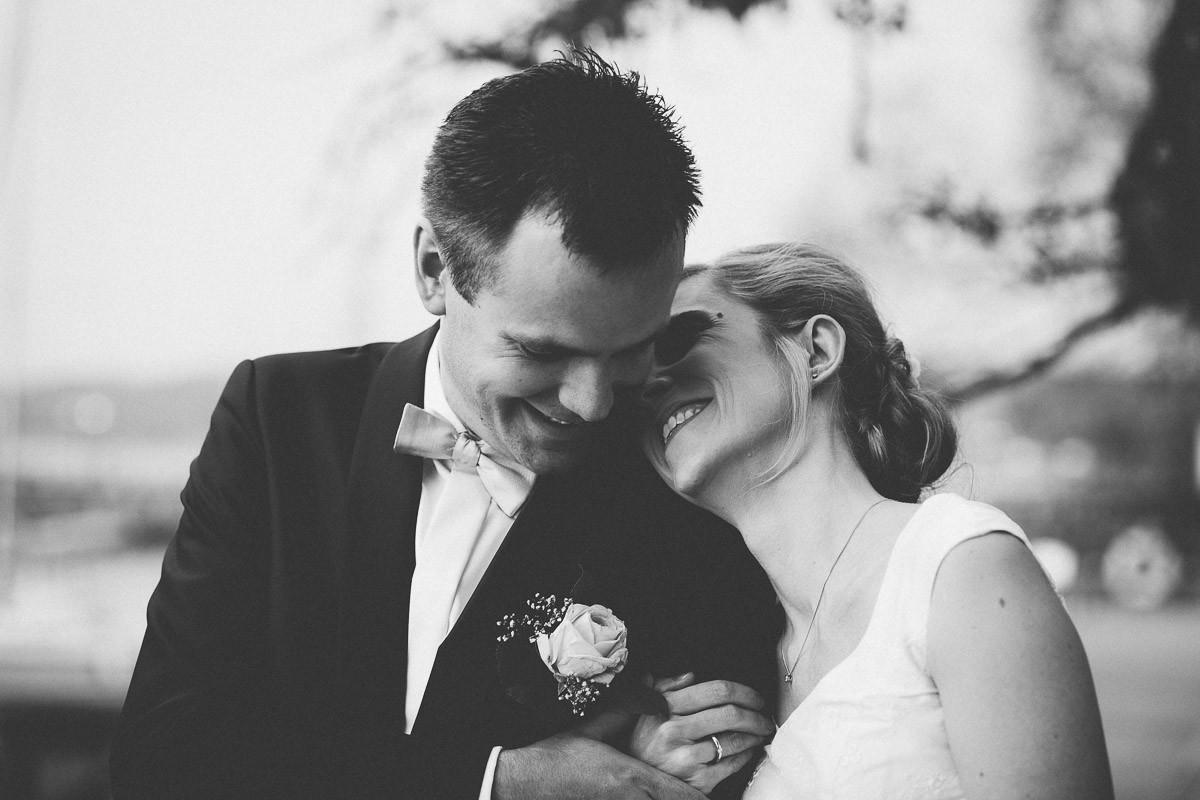 Braut flüstert glücklichem Bräutigam etwas zu