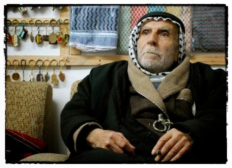 Factory founder Yassar Hirbawi relaxes with a cigarette in the factory's small backroom shop. Behind him hang a sampling of his factory's Kufiyas, as well as key-chains for sale. He says Kufiya is more popular than ever in Palestine. During the first Inti