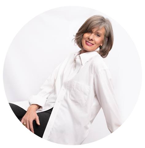 Woman in 60's posing in front of white background with men's white button up