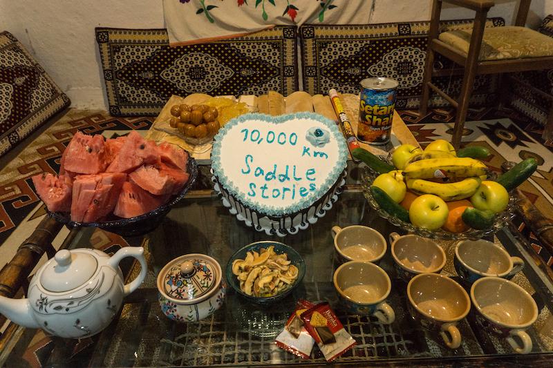 """Das Licht geht an und wir stehen vor einem reich geschmückten Tisch auf dessen Mitte eine Torte mit der Aufschrift """"10,000km Saddle Stories"""" steht. Wir sind sprachlos."""