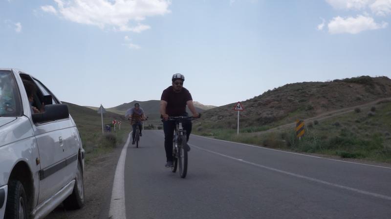 Hossein und Ali teilen sich den Weg: einer im Auto, einer auf dem Fahrrad. Unsere Taschen (zum Glück) auch im Auto! Wenn es für den einen zu anstrengend wird, können sie sich einfach abwechseln.