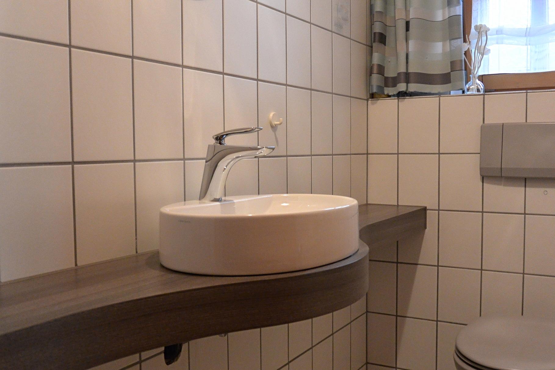 Geschwungene Waschtischkonsole nach Maß für das kleine Gäste WC in Holz-Dekor
