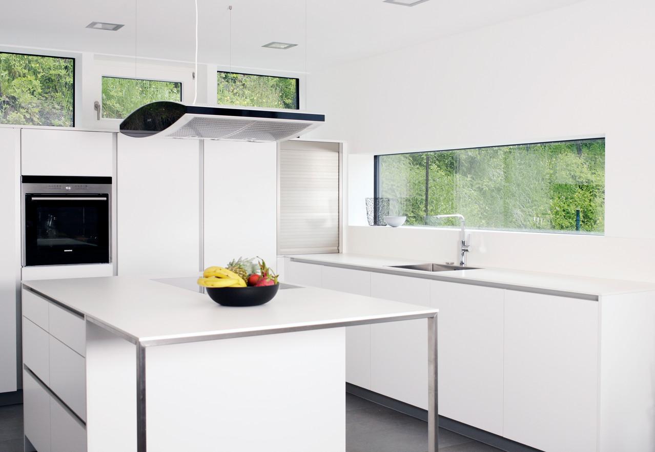 Küche mit weißer Arbeitplatte und weißen Fronten