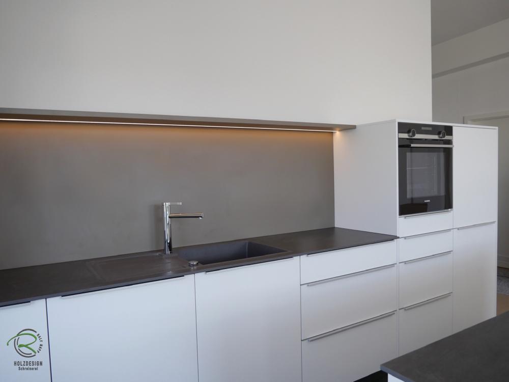Küche mit Insel in weiß mit Keramik-Arbeitsplatte u. indirekt beleuchteter Nischenplatte mit Steckboard Backofen von Siemens u. Liebherr Kühl-Gefrierkombination im Highboard verstaut, Griffleiste auf der Front montiert