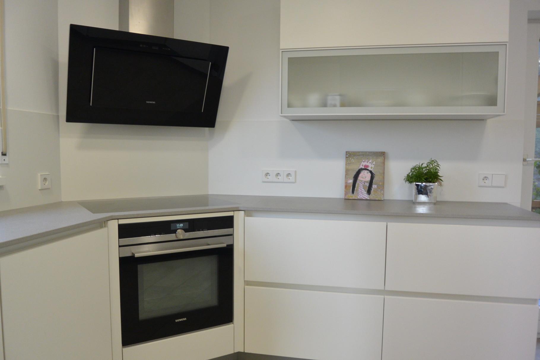 Einbauküche vom Schreiner in weiß matt, Dekton Sirocco Arbeitsplatte, Griffleisten in weiß