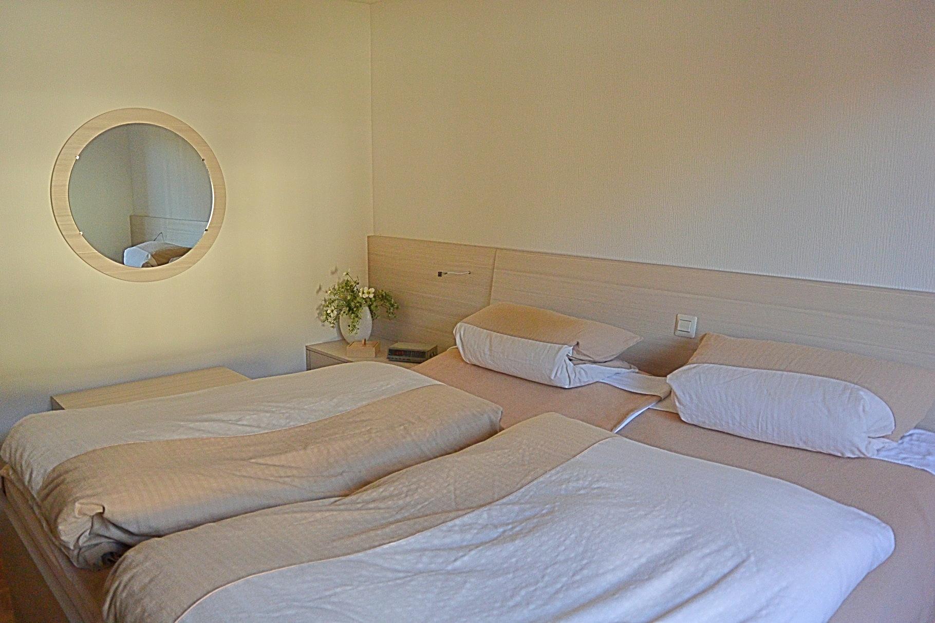 Schlafzimmermöbel mit hellem Dekor, Schiebetürenschrank, ehöhtes Bett und ein schräges Kopfteil