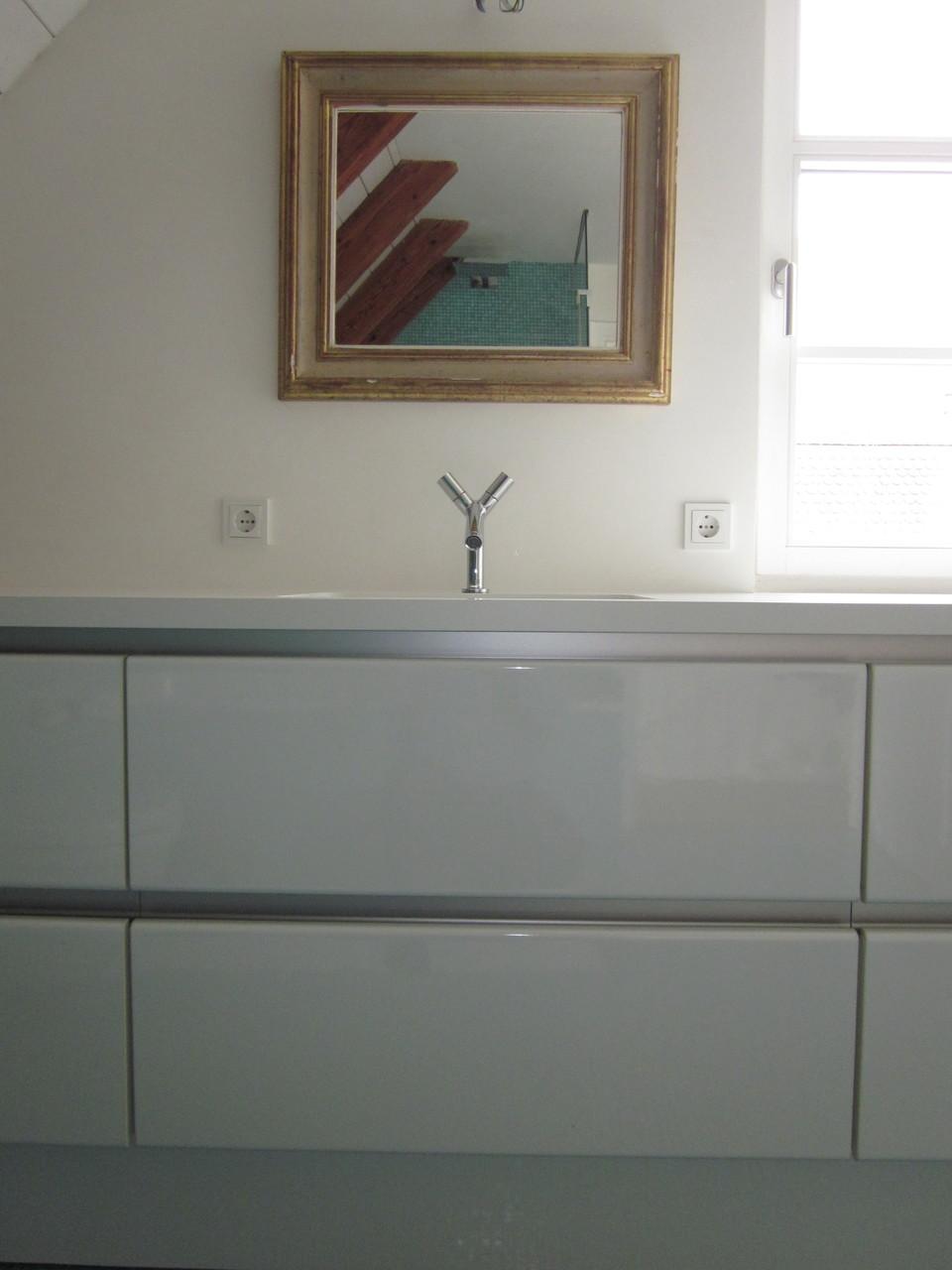 Waschtischunterschrank mit AluminiumGriffmulde in weiß Hochglanz und Waschbecken flächenbündig wie aus einem Guss mit der Waschtischplatte