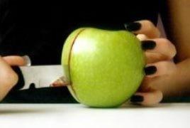 Zdjęcie jabłka krojonego skalpelem_operacja chirurgiczna zostawia ślady w ciele człowieka