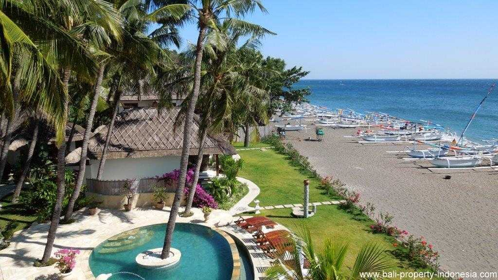 Amed beachfront hotel for sale with various accommodations and facilities.