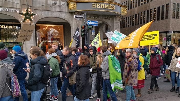 """Auf der Düsseldorfer Luxusmeile Kö verdrängen die Aktivisten die """"Black-Friday""""-Einkäufer - wenngleich auch nur kurzzeitig."""