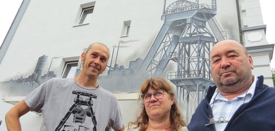 Künstler Jonas Heinevetter vor seinem Werk – zusammen mit Eigentümer und Knappe Norbert Kuschmierz und dessen Frau Sabine.  Foto: Eberhard Franken