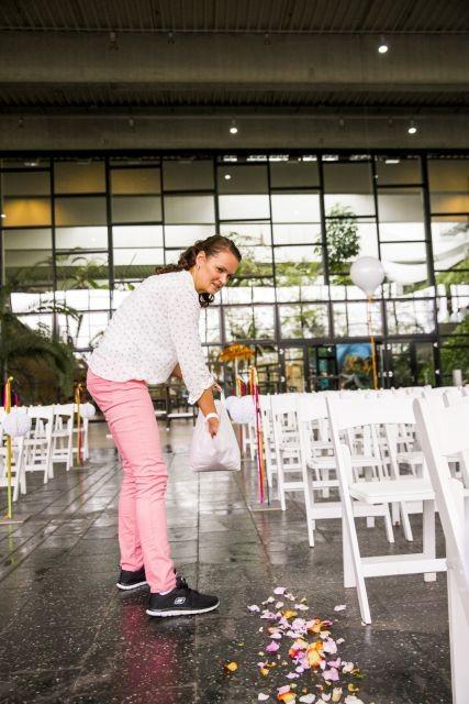 Hochzeitsplanerin streut Blumen für den Mittelgang der freien Trauung